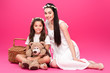 Leinwandbild Motiv beautiful happy mother and daughter in white dresses sitting with teddy bear and picnic basket on pink