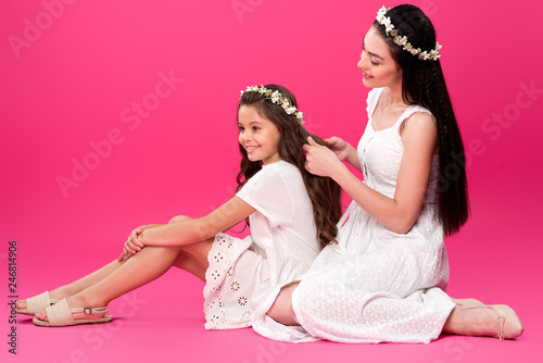 Leinwandbild Motiv happy young mother plaiting braid to beautiful smiling daughter on pink