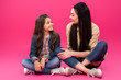 Leinwandbild Motiv full length view of smiling mother and daughter sitting and talking on pink