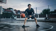 Athletic Young Male Basketball Player Dribbles and Throws the Ball in Crouched Position in a Residential Neighborhood Fenced Streetball Court.