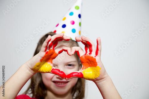 Foto Murales Девочка в колпачке, показывает ладошки в краске