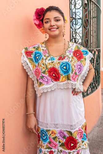 Pretty and colorful Mayan girl in Yucatan. Young smiling girl inviting tourism to visit Merida in the Yucatan peninsula - 246857974