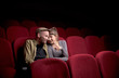Leinwanddruck Bild - Young cute couple sitting alone at red movie theatre and having fun