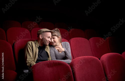 Leinwanddruck Bild Young cute couple sitting alone at red movie theatre and having fun