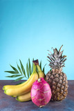 Assorted tropical fruits pineapple, mango, dragon fruit, on stone background. Group of exotic tropical fruits. Vegetarian healthy concept