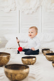 Little boy playing with Tibetan singing bowls sitting on the bed - 246875727