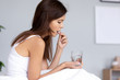 Leinwandbild Motiv Millennial ill sick woman taking painkiller medicine to relieve headache pain sit on bed in the morning, young girl holding sleeping abortion pill and glass of water suffering from chronic insomnia