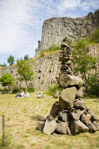 Man made stone tower outdoor, with unique basalt rock formation wall background. - 246890798