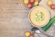 Homemade potato and leek soup. Top view table scene on a light brown wood background with copy space.