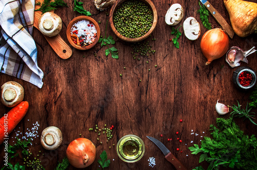 Foto Murales Ingredients for cooking green lentils with mushrooms and vegetables, spices and herbs, vintage wooden kitchen table background, place for text. Vegan or vegetarian food, clean food concept