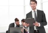 Executive businessman with clipboard standing in office - 246922329