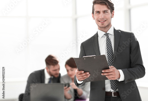 fototapeta na ścianę Executive businessman with clipboard standing in office