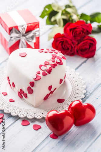 Leinwandbild Motiv Marzipan white cake in the shape of a heart with red hearts. As the decoration bouquet of red roses a gift from the ribbon. Wedding or valentines day concept.