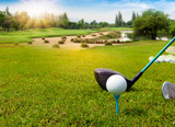 Golf ball on tee ready to be shot in green grass on blurred beautiful landscape of golf course with sunrise,sunset time on background.