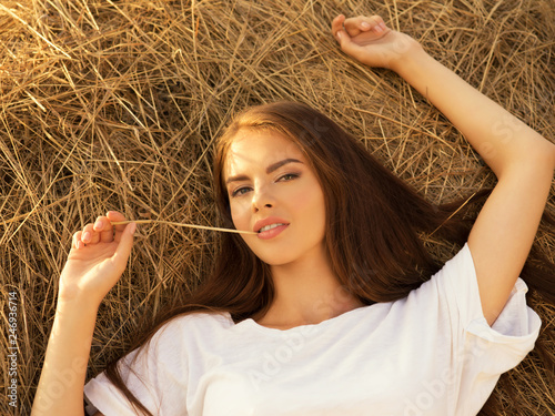 Foto Murales Beautiful young woman is relaxing on the haystack.