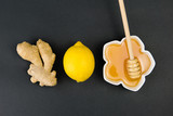 Healthy food concept, honey with dipper, lemon and ginger,  on a black background - 246943111