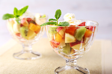 Diet-Fresh tasty mix fruit salad in the bowl on the wooden table, healthy breakfast, weight loss concept.