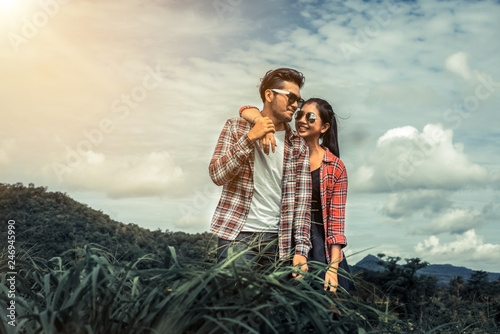 Leinwandbild Motiv Happy couple take a romantic walk in green grass field on the hills. Travel and honeymoon concept.