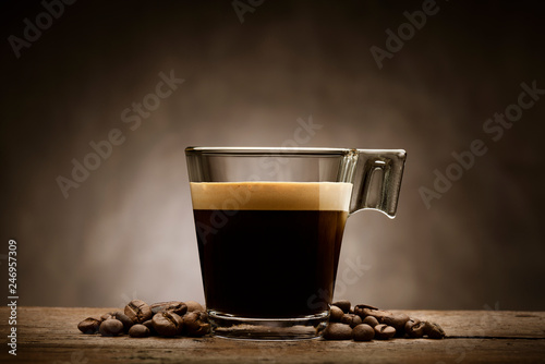 Black coffee in glass cup with coffee beans on wooden table © winston
