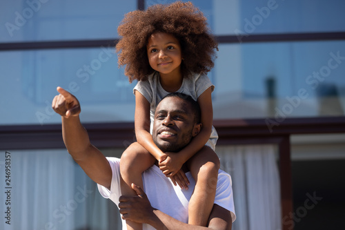 Leinwandbild Motiv Happy single african dad holding cute kid daughter on shoulders outdoors looking forward showing good future vision playing outside, little child girl embracing loving black father dreaming together