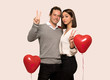 Couple in valentine day smiling and showing victory sign with both hands over isolated background