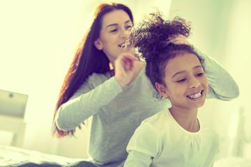 Caring responsible mom brushing hair of her mulatto daughter. © Viacheslav Iakobchuk