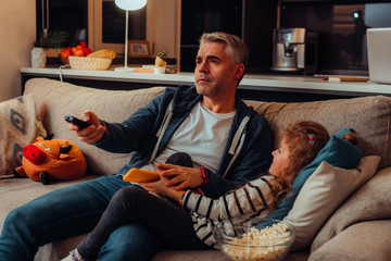 Handsome grey-haired man in sport clothing choosing channels on tv
