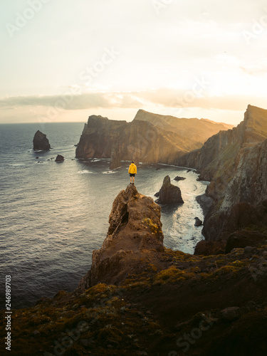 Foto Murales  Travel man alone on the edge cliff se díva na oceán, hiking adventure lifestyle extreme vacations sunset landscape in Portugal, Madeira