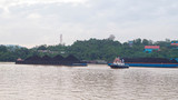 tugboat with barge full of coal cruising Mahakam River, Samarinda, Indonesia - 246997704