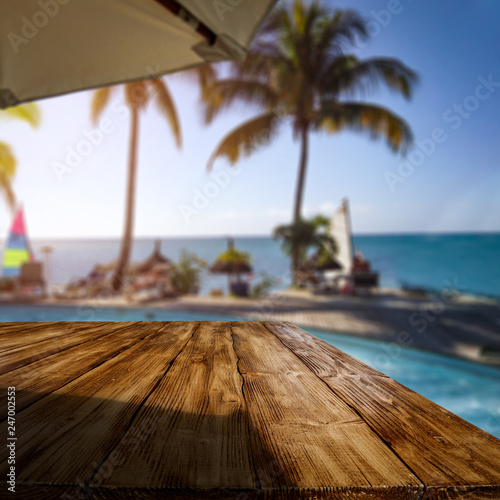 Wooden desk of free space and exotic landscape of sea and palms  - 247002553