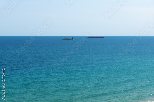 blue sea surface with small ships on the horizon