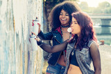 two urban girls multi-cultural teenagers painting graffiti artwork on a city wall
