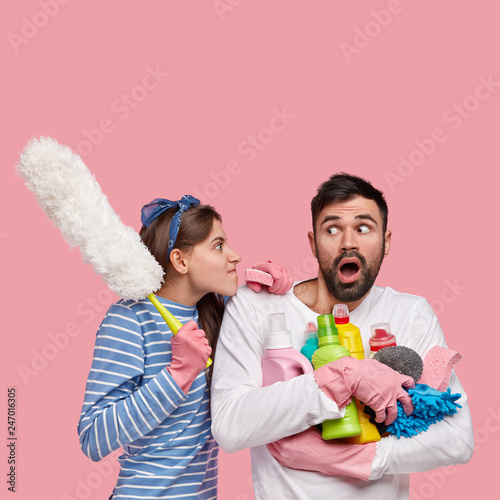 Leinwandbild Motiv Vertical shot of dissatisfied woman looks angrily at husband, reproaches of laziness, carries cleaning supplies, isolated over pink background with empty space for your advertisement or text