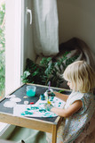 Adorable little girl playing with green paint at home near the window. - 247026583