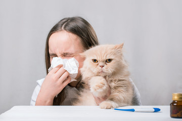 A girl holds a cat and blowing his nose in a paper handkerchief