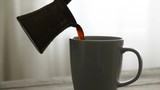 Fresh Coffee pouring into transparent cup on table. Slow motion video - 247030179