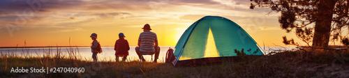 Leinwandbild Motiv Family resting with tent in nature at sunset