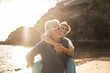 adults caucasian people couple in love with man carrying the woman and both smile and laugh a lot - sunset and backlight at the beach - vacation lifestyle married forever concept for happy matures