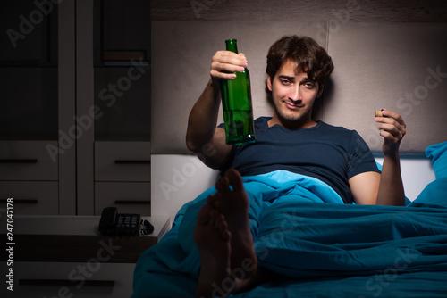 Leinwandbild Motiv Man drinking in the bed under stress