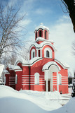 Red Christian church in the winter, snow on the roof