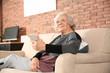 Leinwandbild Motiv Elderly woman using smartphone on sofa in living room