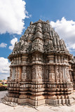 Belavadi, Karnataka, India - November 2, 2013: Veera Narayana Temple. Closeup of the wiht statues heavy decorated tower on one of three brown-stone Vimanams of the complex under cloudscape.