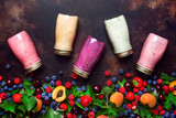 Healthy and useful colorful berry cokctalis, smoothies and milkshakes with yogurt, fresh fruit and berries on brown kitchen table background, flat lay, top view