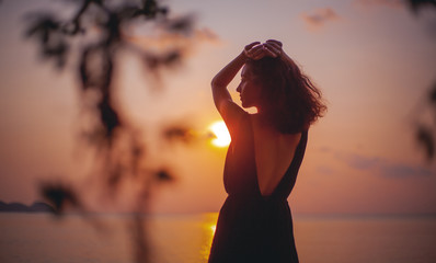 Young beautiful sensual woman in a stylish dress with an open back is standing on the seashore at sunset in the rays of the sun, beauty and fashion, leisure and travel concept