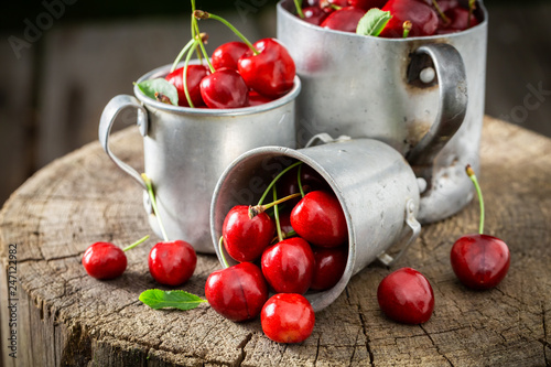 Leinwanddruck Bild Ripe sweet cherries in the old metal mug