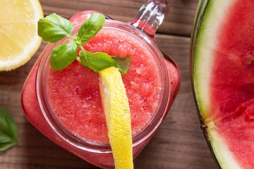 Fresh watermelon smoothie in the mason jar on wooden background. Summer, healthy organic food concept.