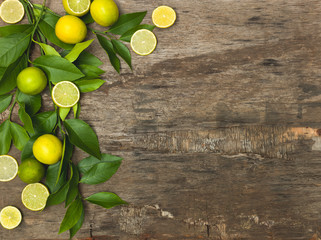 fresh, juicy lemons and limes lie on an old wooden background