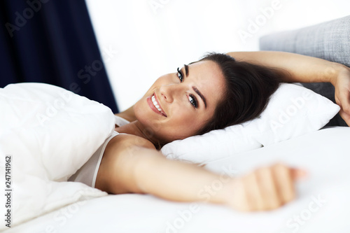 Leinwanddruck Bild Young beautiful woman waking up in her bed fully rested