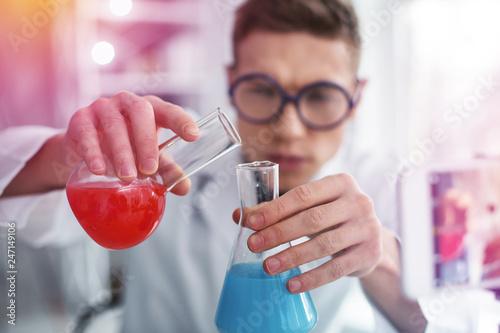 Leinwandbild Motiv Close up of student studying chemistry holding test tubes with colorful liquid