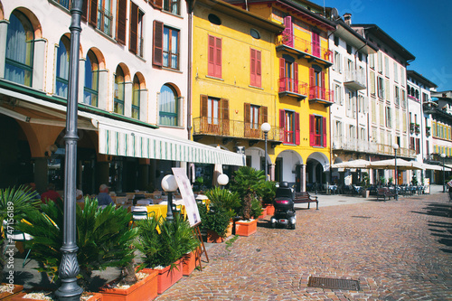 Beautiful Italian park with yellow houses. Cafes near the coast of Pisogne, Italy.